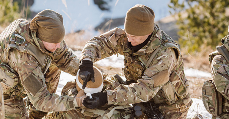 Two soldiers in uniform help treat a third injured soldier