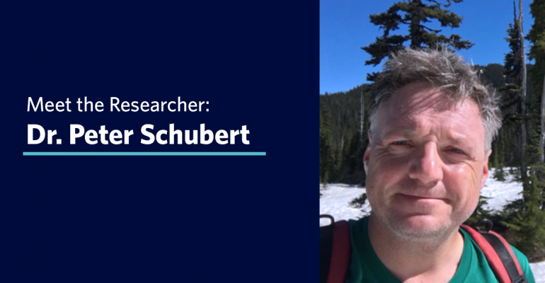 """Dr. Peter Schubert hiking in the snowy mountains of Garibaldi, with text that says """"Meet the Researcher: Dr. Peter Schubert"""""""